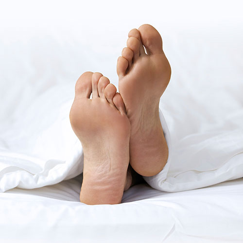 Man's feet whilst asleep in bed